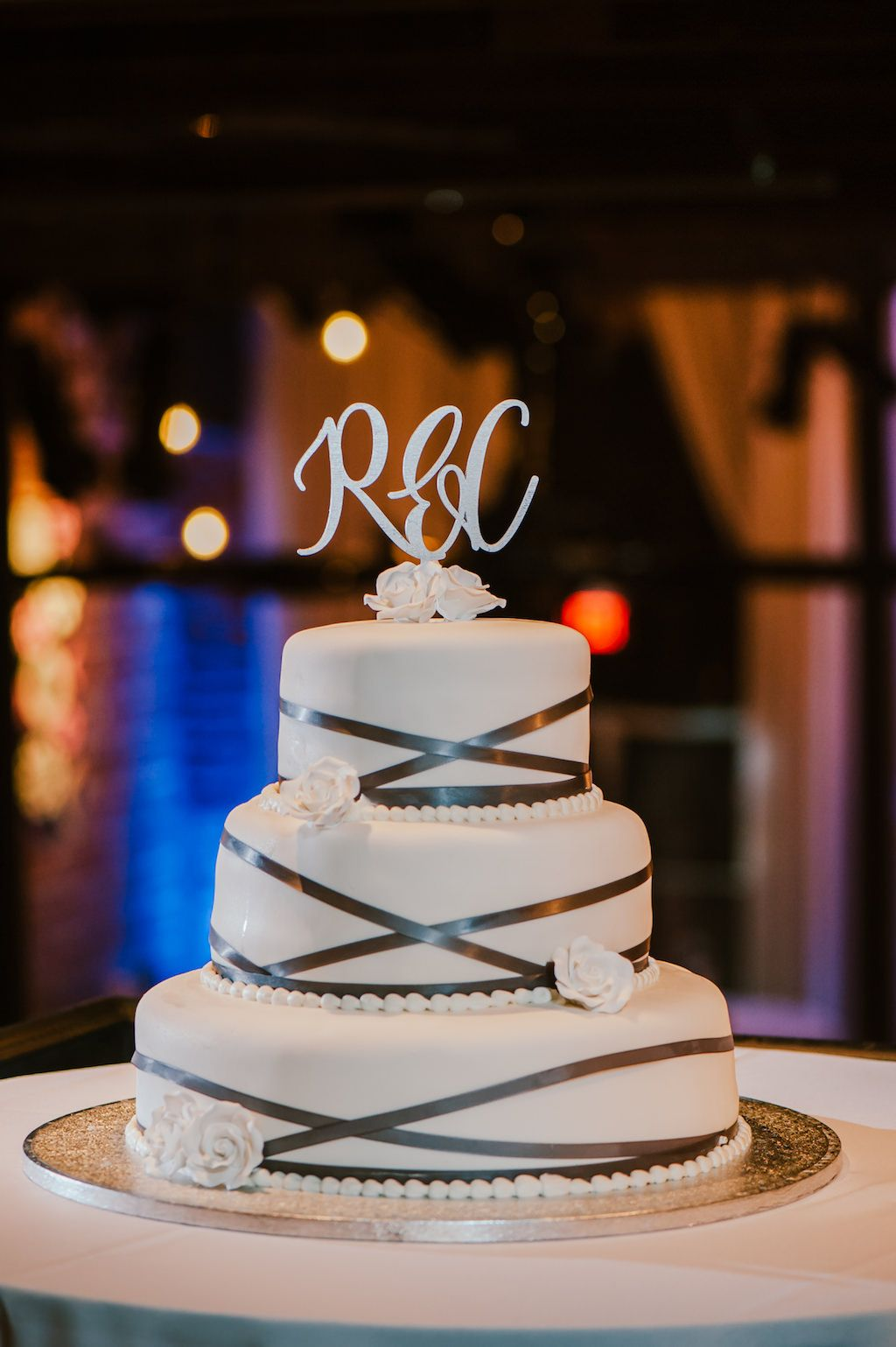 White wedding cake with ribbon icing and laser cut topper