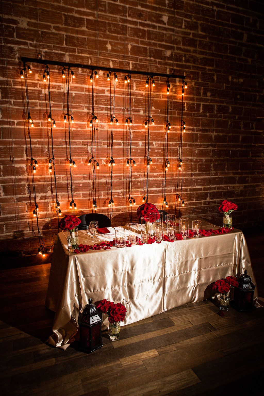 Glam red and gold sweetheart table with string light backdrop at St. Pete wedding venue NOVA 535