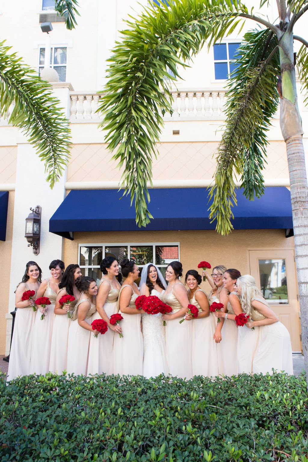 Glam champagne downtown St. Pete bridal party with red bouquets