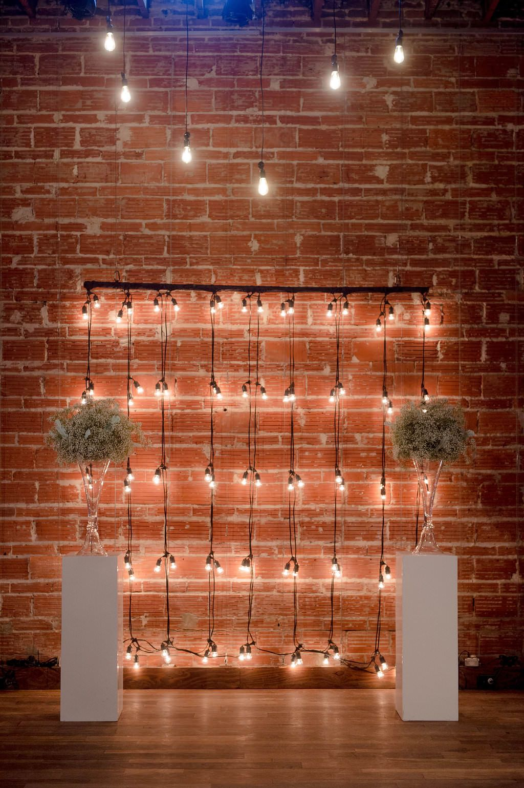 Industrial string light and baby's breath arrangement ceremony decor