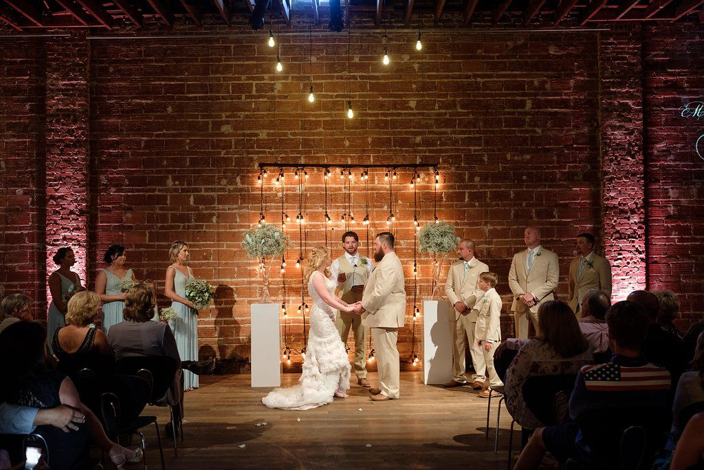 Industrial wedding ceremony with string light backdrop in downtown St. Pete at NOVA 535