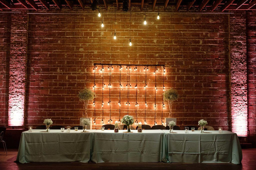 Industrial sweetheart table with string light backdrop at NOVA 535