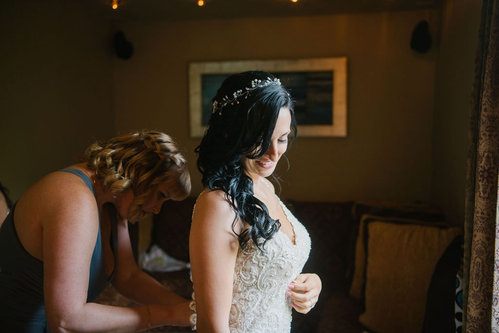 Bride in lace wedding dress getting dresses
