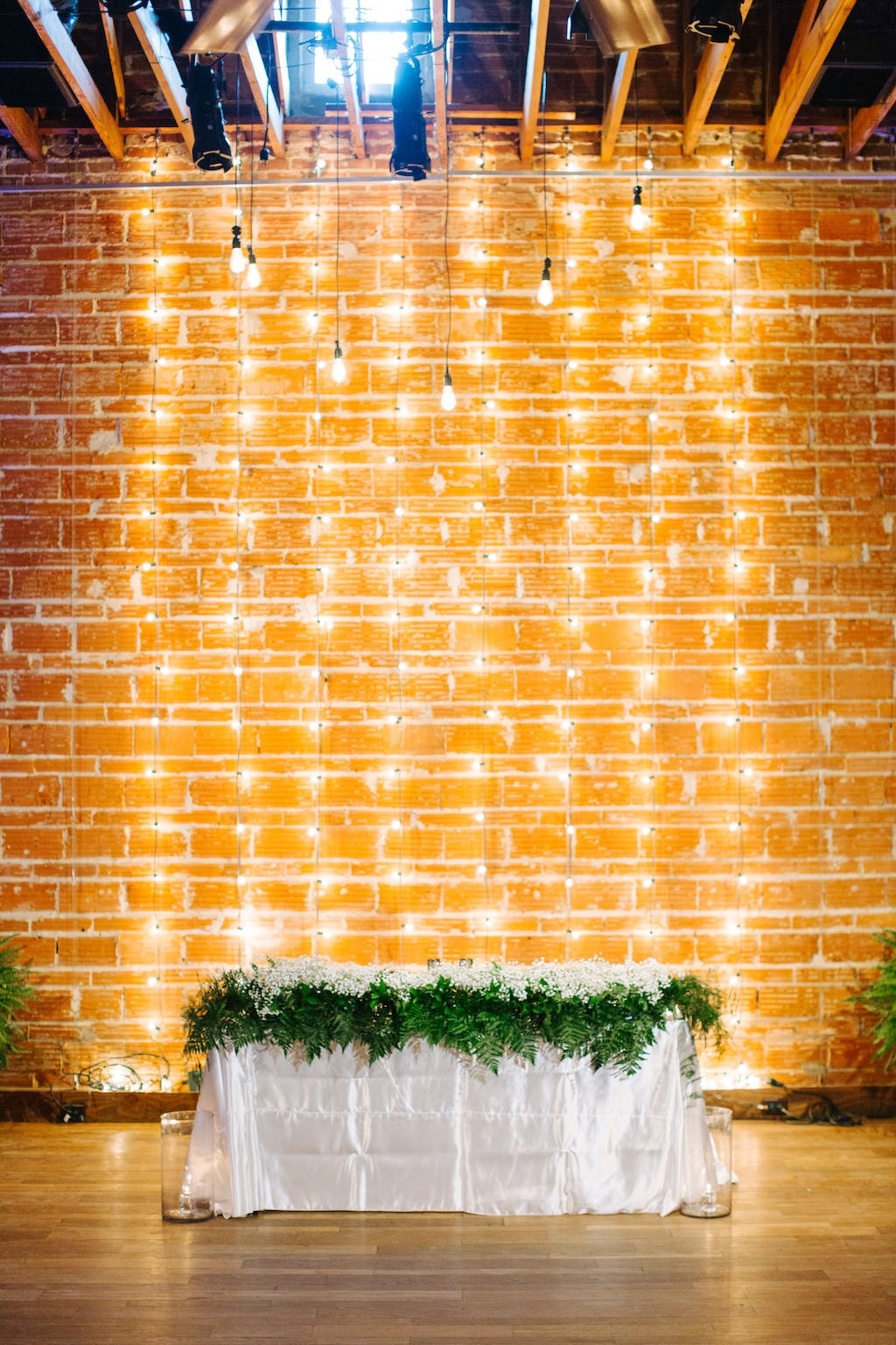 Modern, Romantic Reception and Florida Wedding Decor, Sweetheart Table, with Babies Breath Garland Florals, String light Backdrop on Exposed Brick Wall | | Tampa Bay Premier Wedding Venue NOVA 535 in Downtown St. Pete