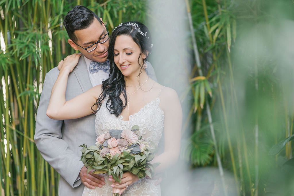 Bride in lace wedding dress with blush and gray bouquet with groom in gray suit
