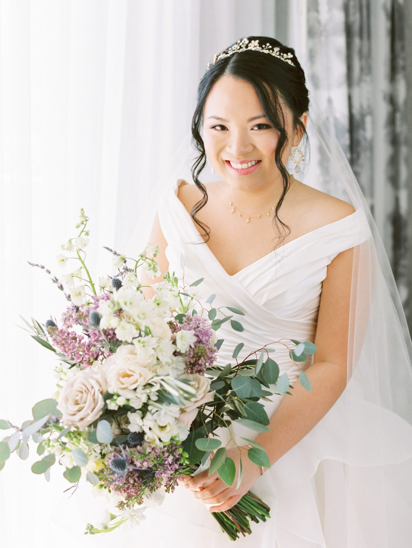 Bride in off the shoulder gown and tiara with white and purple bouquet