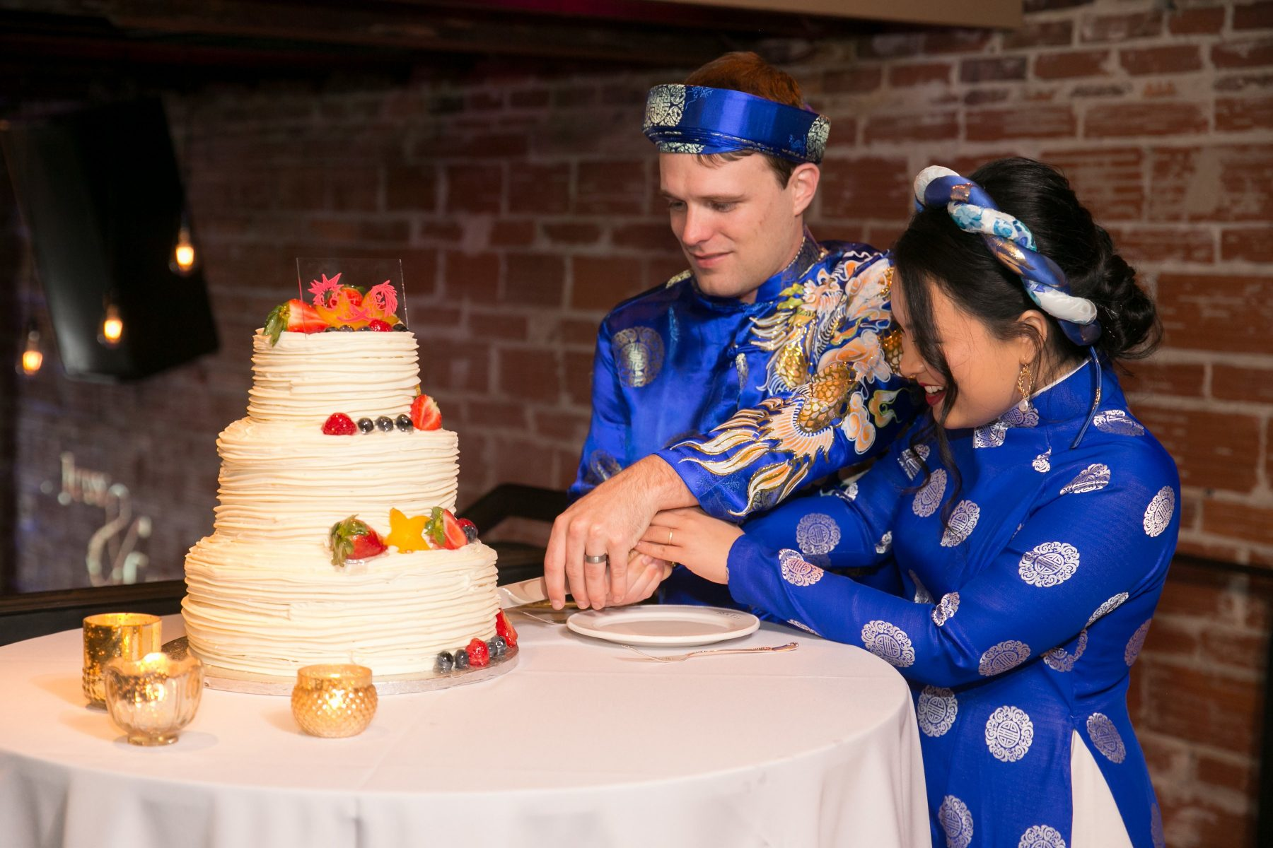 Bride and groom in traditional Vietnamese wedding outfits cutting cake | Multi-Cultural St Pete Wedding