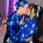 Bride and groom in traditional Vietnamese wedding outfits kissing