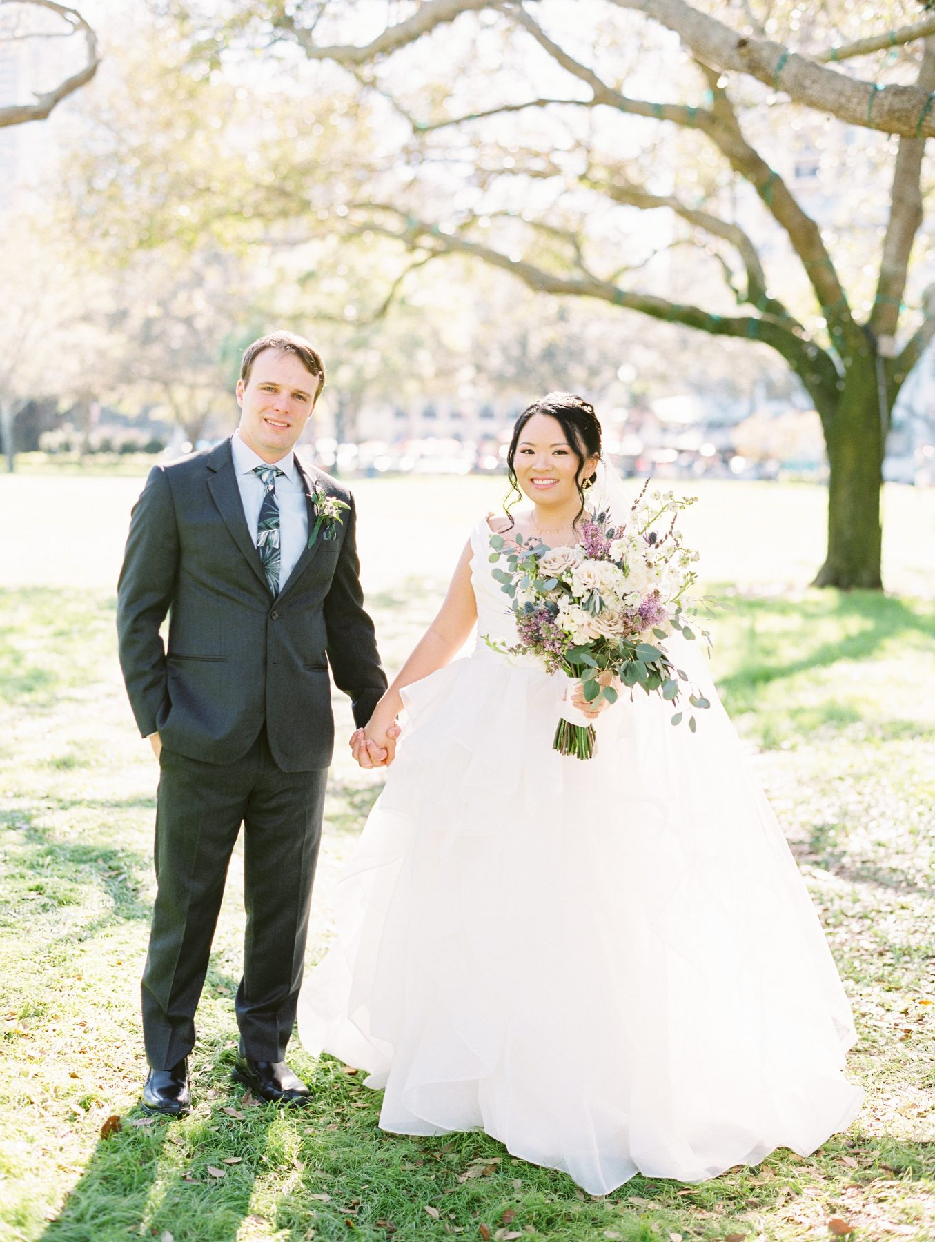 Bride with white and purple bouquet with groom under tree