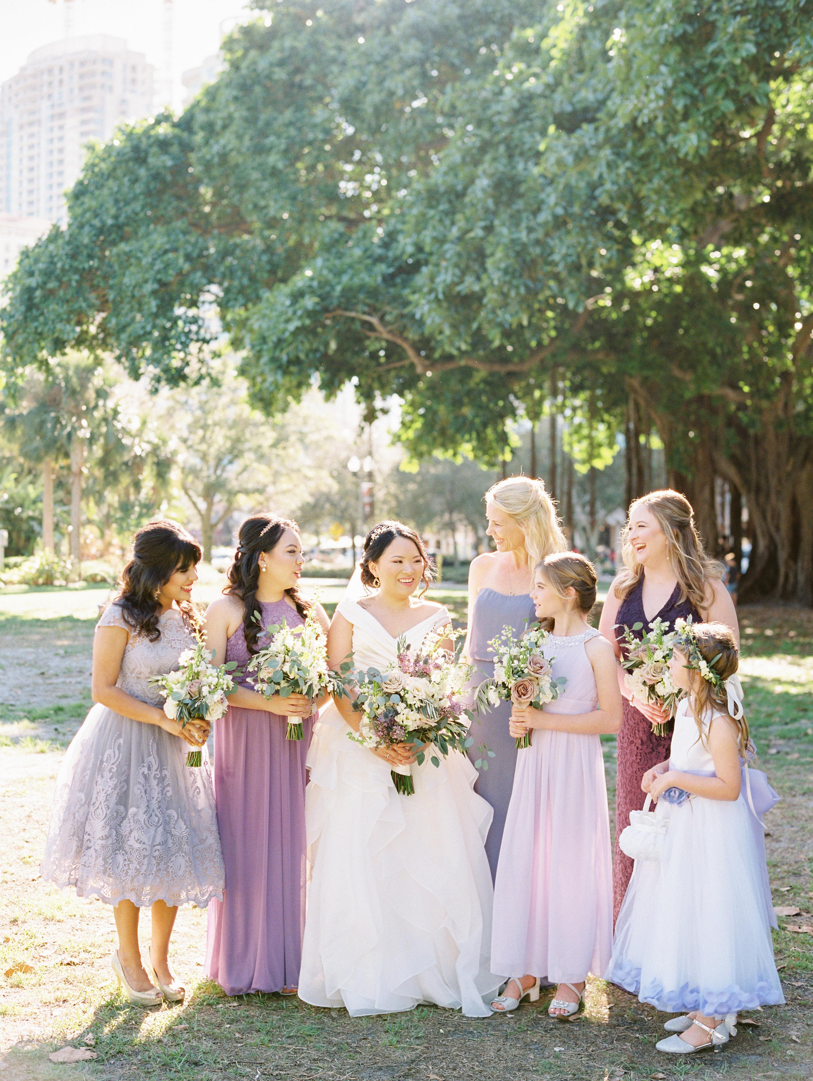 Bridesmaids in mismatched purple dresses