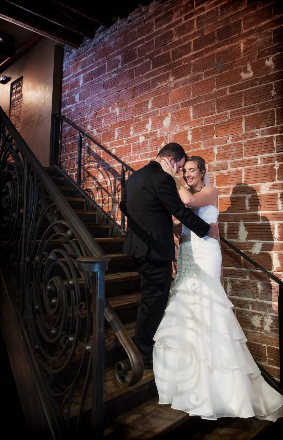 Vintage Florida Bride and Groom First Look on Staircase against Exposed Red Brick Wall | Downtown St. Pete Unique Wedding Venue NOVA 535