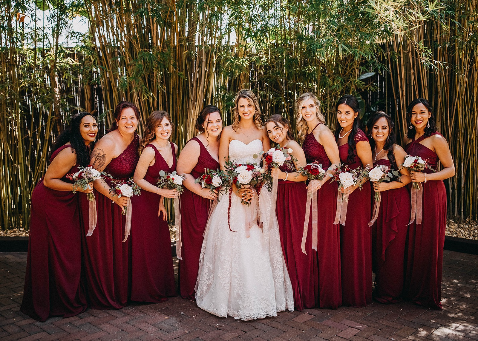 Beautiful Deep Red Maroon Bride and Bridesmaids in Long David's Bridal Dresses in outdoor bamboo courtyard at historic Tampa Bay wedding venue NOVA 535 in Downtown St. Pete