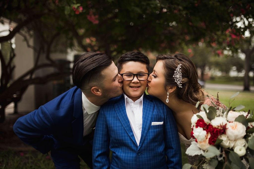 Bride and groom kissing ring bearer