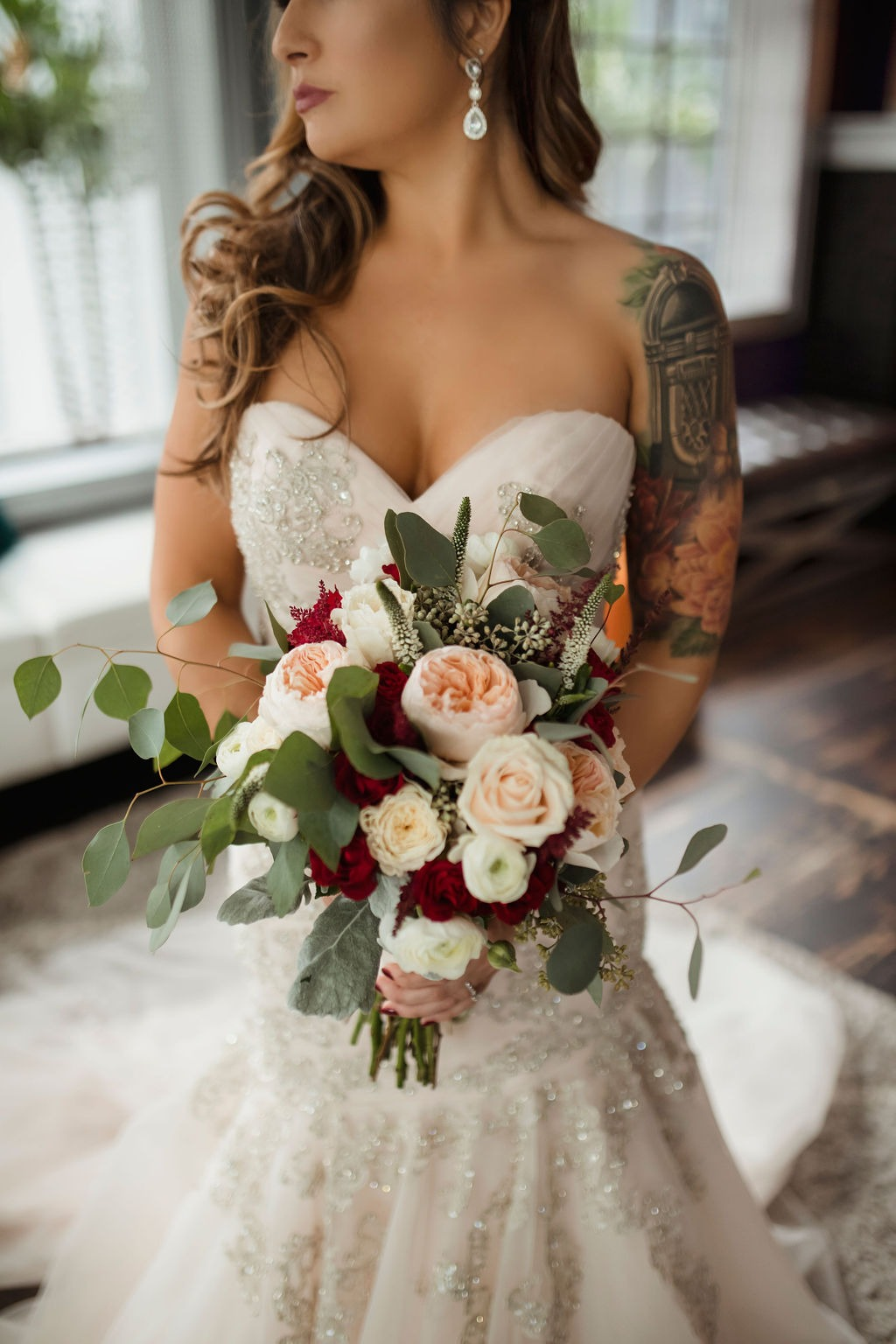 Bride in embellished strapless wedding dress with blush and red bouquet